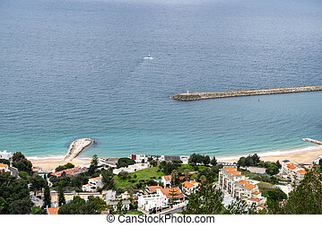 Beautiful aerial view of Sesimbra, Portugal - as seen from the castle on the hill, with lighthouse and jetty in photo
