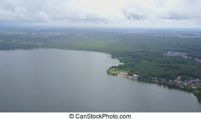 Beautiful aerial view of the azure lake surrounded by forest. Lush green forest on the bank of a lake, top view, aerial