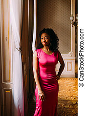 Beautiful African-American girl in red dress posing at the luxurious apartments