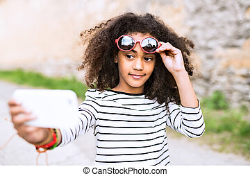 Beautiful african american girl with smart phone, taking selfie.