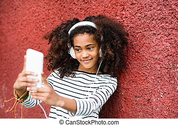Beautiful african american girl with smart phone taking selfie.