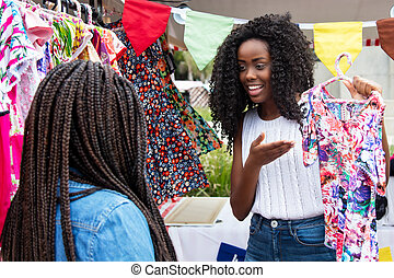 Beautiful african american market vendor presenting clothes ...