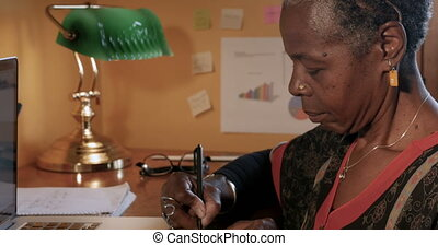Beautiful African American mature woman writing on yellow...