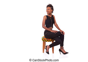 Beautiful African American woman sitting on a stool isolated on white background