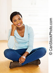 african american woman sitting on floor in new house