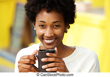 Beautiful african american woman smiling with cup of a coffee