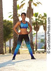 Beautiful african american woman standing outside in sportswear