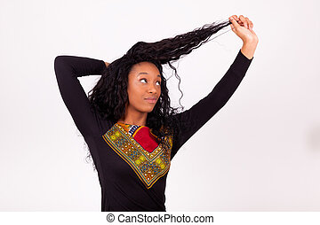 Beautiful African American woman touching her curly hairs