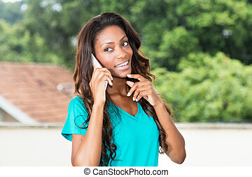Beautiful african american woman with long hair at mobile phone