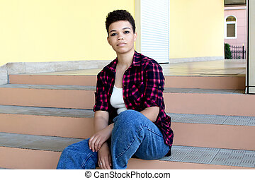 beautiful african american woman with short hair, outside sitting on the stairs, lifestyle