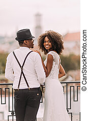 Beautiful african bride and stylish groom in hat holding hands on the rooftop