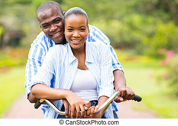 african couple riding bicycle together