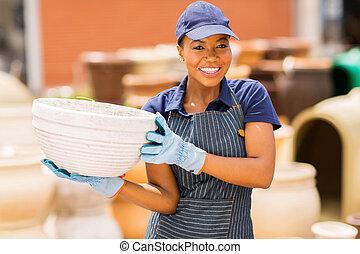 african garden center worker holding clay pot