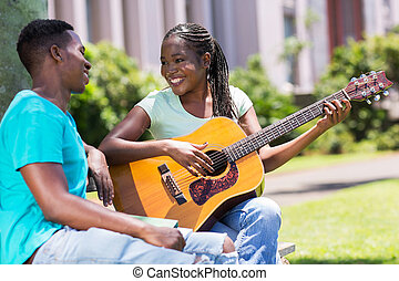 african girl playing guitar for her boyfriend