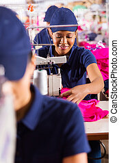 african textile worker using sewing machine