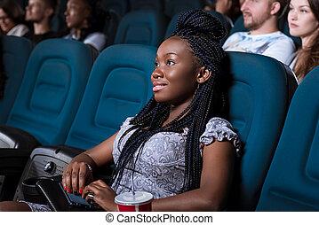 Beautiful African woman enjoying a movie