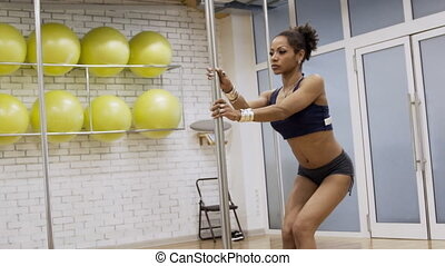 Beautiful African woman holds pole and gently dances in fitness room.