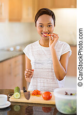african woman making salad in kitchen