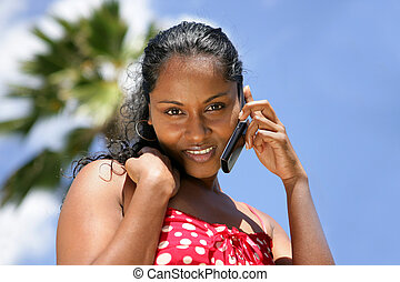 beautiful African woman on vacation talking on her cell