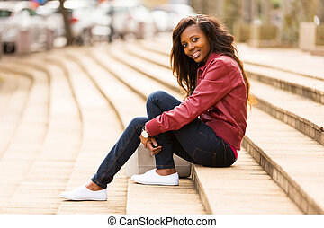 african woman outdoors sitting on steps