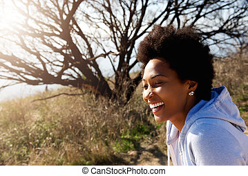 Beautiful african woman sitting outdoors and laughing
