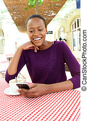 Beautiful african woman using cell phone at cafe