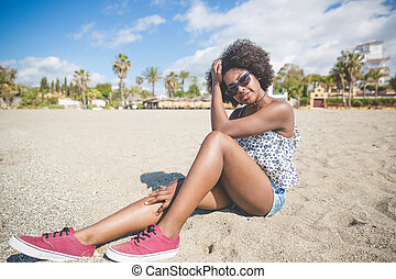 Beautiful afro american woman sitting on beach