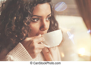 Beautiful afro american woman taking a sip of tea