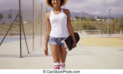 Beautiful afro female skater wearing shorts - Beautiful afro...