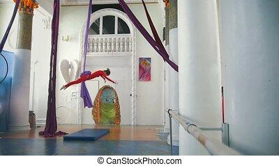 Beautiful air dancer makes acrobatic elements on aerial silk...