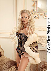Beautiful alluring sexy woman portrait in black fashion lingerie and fox fur coat posing by luxury armchair in modern interior.
