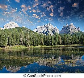 Beautiful alpin landscape. Mountain peaks reflected into a lake