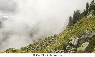 Beautiful alpine mountains covered with clouds