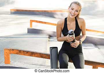 Beautiful amazing happy young sports woman holding water outdoors.