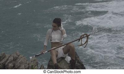 Beautiful amazon woman warrior wearing white outfit sitting...