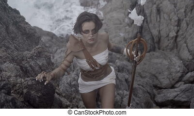 Beautiful amazon woman warrior wearing white outfit and brown leather swordbelts climbing on the rocks with rifle over stormy sea background