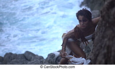 Beautiful amazon woman warrior wearing white outfit and brown leather swordbelts climbing on the rocks with rifle over stormy sea background - video in slow motion