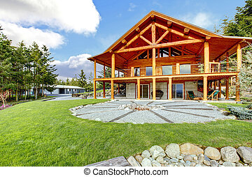 Beautiful American classic log cabin with porch and circle fire pit.