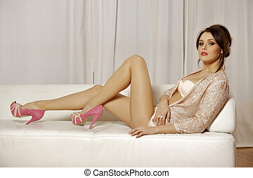 Beautiful and attractive female brunette woman posing in pink lingerie on the sofa