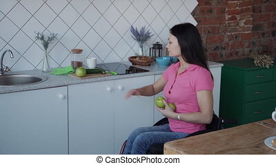 Adult woman in wheelchair cleaning fresh apple on kitchen -...