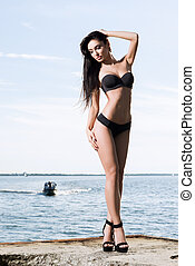Beautiful and fit fashion model in a swimsuit on a pier