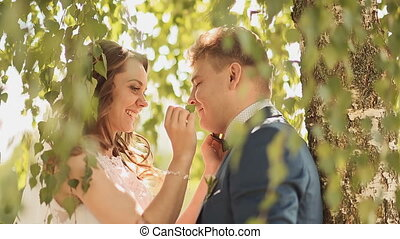 Beautiful and happy bride and groom under the branches of the birch trees rejoice together.