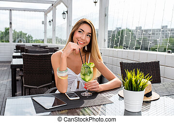 Beautiful and happy girl in summer in cafe, smiling, dreaming and fantasizing, thinking. On table is a cocktail, a tablet mobile phone. Concept of date and meeting in restaurant, resting after work.