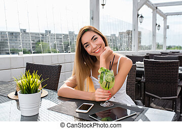 Beautiful and happy girl smiling in summer cafe. On the table is an electronic tablet phone. A glass of lime green drink. Posing while waiting for friends. Breakfast after lunch in the open air.