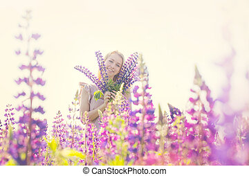Beautiful and happy woman with bouquet of lupines on the field