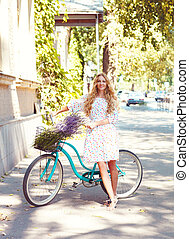 Beautiful and happy young woman with bicycle