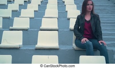 Beautiful and passionate girl in a biker jacket alone sits in an empty stadium. Girl's hair develops in the wind.