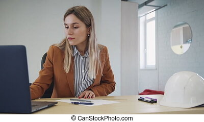Beautiful and professional collar worker sitting behind table inside workplace office with modern bright interior. Woman checking information about architect project on laptop and making blueprint