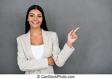 Beautiful and reliable. Smiling young businesswoman looking at camera and pointing away while standing against grey background