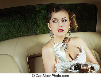 Beautiful and rich superstar girl sitting in a retro car and eating a chocolate